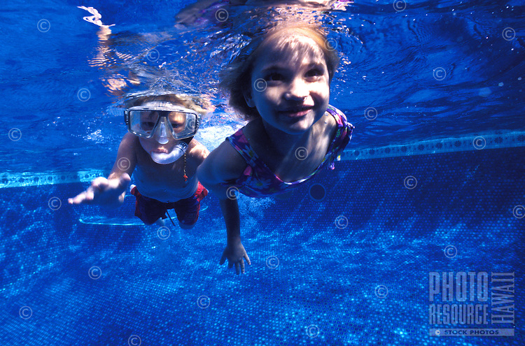 Girl and boy playing and swimming under water in a pool