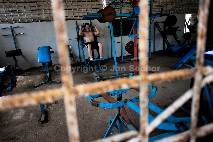 "A young Cuban man trains at a bodybuilding gym in Alamar, a public housing complex in the Eastern Havana, Cuba, 9 February 2011. The Cuban economic transformation (after the revolution in 1959) has changed the housing status in Cuba from a consumer commodity into a social right. In 1970s, to overcome the serious housing shortage, the Cuban state took over the Soviet Union concept of social housing. Using prefabricated panel factories, donated to Cuba by Soviets, huge public housing complexes have risen in the outskirts of Cuban towns. Although these mass housing settlements provided habitation to many families, they often lack infrastructure, culture, shops, services and well-maintained public spaces. Many local residents have no feeling of belonging and inspite of living on a tropical island, they claim to be ""living in Siberia""."