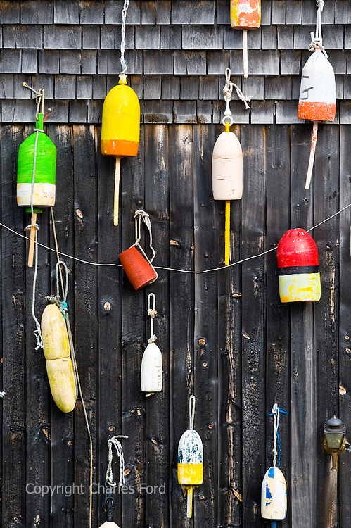 Colorful lobster buoys hanging on the side of a wooden building.