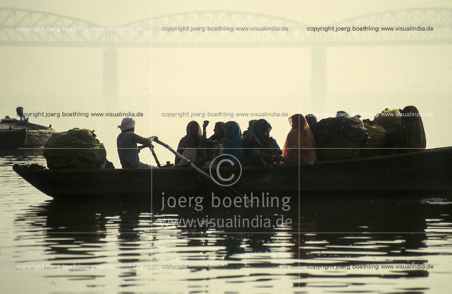 INDIA, Benares Varanasi,<br /> people in wooden ferry boat cross river Ganga, behind large highway bridge in morning fog