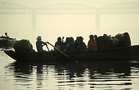 INDIA, Benares Varanasi,<br /> people in wooden ferry boat cross river Ganga, behind large highway bridge in morning fog