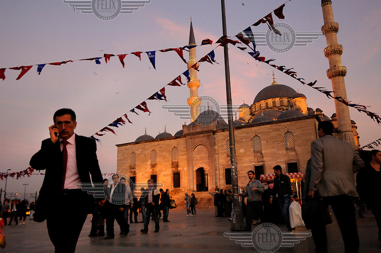 A man talking on his mobile phone as he crosses the Eminonu Meydani, passing the Yeni Cami - the four hundred year old 'New Mosque', which stands by the Golden Horn.