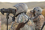 Hunters with riding gear and binoculars and scope.