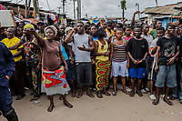 MONROVIA, LIBERIA - AUGUST 23, 2014:   Residents wait for relatives to bring them food from outside of the quarantined area, during the fourth day of the government's Ebola quarantine on the West Point neighbourhood on August 23, 2014 in Monrovia, Liberia.  Liberia&rsquo;s government announced Friday night that it would lift an Ebola quarantine on a large slum here in the capital, 10 days after attempts to cordon off the neighborhood from the rest of the city sparked deadly clashes and fueled doubts about President Ellen Johnson Sirleaf&rsquo;s ability to handle the outbreak.<br /> photo by Daniel Berehulak