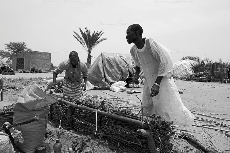 Sani Daleba, South Darfur, August 1, 2004.A recently arrived family builds a shelter. Protected by a small police force, a few hundred 'Fur' farmers have begun returning to their small town, completely destroyed two months ago by Janjaweed attacks.