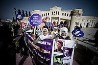 Les femmes de Nusaybin protestent ce jour là contre la construction du mur frontière. 1,3 km ont été érigés dans la ville pour renforcer la séparation avec Qamislo sa jumelle syrienne. Le cortège part du centre culturel kurde de la ville pour rejoindre le mur et le grillage de la frontière. Les banderoles sont écrites en turc, en arabe, en kurde et en araméen. Les figures sont les effigies féminines de la lutte politique pour les droits de la femme depuis le XIX siècle.