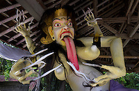 Ogoh-ogoh (demon) of a leyak (follower of Rangda, divine witch, linked to Durga / Kali, shakti of Shiva), Central Bali.  Balinese New Year called Nyepi (around march according to lunar calendar),  is a silent day of meditation and spiritual purification. One day before exorcist rituals are held for purification and balance of polar powers of the universe, first at noon by a priest (exorcism called Caru or Tawur Agung) and later on after sunset in a popular, carneval-like procession of Ogoh-Ogoh, symbolizing bhuta kali (demon, bad spirits,bad habits),  so all the bad spirits leave the village and the island.  Loud, rhythmic music and special performances are part of the procession called Ngerupuk. Road crossings are major spots of exorcism and special ogoh-ogoh performance, since demons often like to dwell here. At Nyepi, the following day, there is 24 hours silence, no vehicle or people on the street, no light or fire, no working  all the bad spirits should think, the island is abandoned and leave the island. Day after Nyepi is a day of reconciliation  new year starts purified.