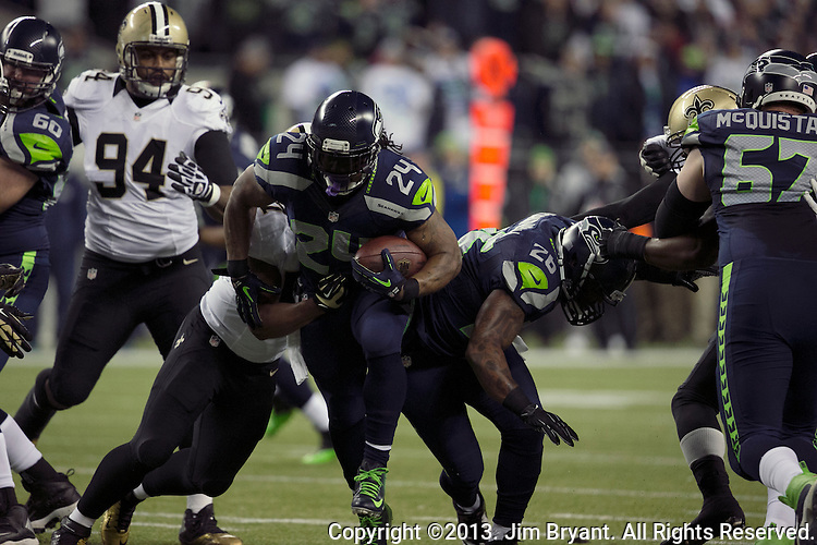 Seattle Seahawks running back Marshawn Lynch runs up the middle for a two-yard gain against New Orleans Saints during the second quarter at CenturyLink Field in Seattle, Washington on December 2, 2013. Lynch rushed for 45 yards as Seahawks became the first team to clinch a spot in the NFC playoffs with a 34-7 victory over the New Orleans Saints.©2013. Jim Bryant Photo. ALL RIGHTS RESERVED.