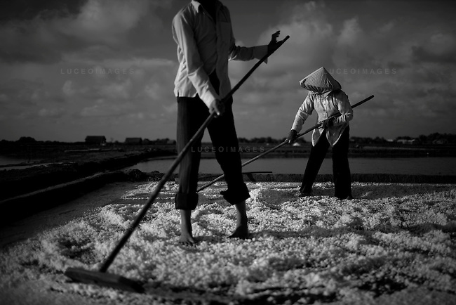 Salt people of Vietnam..Lan Pham, 40, right, works on her family's salt farm with her nephew Phong Quyen, 16.  They use long rakes to break up the salt before scraping it into piles for transport...Farmers harvest salt cultivated in rice-patty like fields in Ben Tre, a village in southern Vietnam. The salt season usually begins in January and ends in March as these are the driest months. Photo taken Friday, March 21, 2008. Kevin German / kevin@kevingerman.com