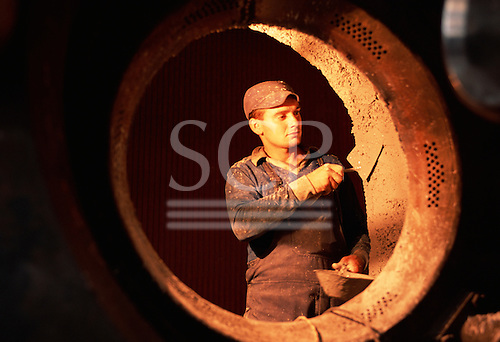 Belgrade, Serbia, Yugoslavia. Man working at an urban heating plant, using a trowel with fire cement inside a boiler.