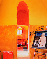 The studio is painted in vibrant tones of yellow and orange with an arch above the doorway picked out in bright red