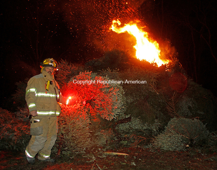 Woodbury, CT011814MK05 Woodbury's Lieutenant Garns uses a flare to ignite the mountain of trees as over a hundred local fire watchers came to view the blaze during the Woodbury Volunteer Fire Department's annual Twelfth Night Christmas Tree Burn in Woodbury on Saturday evening.  Fire chief Morgan said that 300 trees had been collected for the burn which has been held annually for nearly twenty-five years.  Michael Kabelka Republican-American