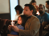 """NWA Democrat-Gazette/CHARLIE KAIJO Daniel Whitfield and Kaitlynn Whitfield, 6, of Bella Vista hold a candle during a vigil, Thursday, August 8, 2019 at the All Saints' Episcopal Church in Bentonville.<br /> <br /> Moms Demand Action of Benton County held a candle light vigil to honor the victims of the El Paso, TX. and Dayton, OH. shootings that took the lives of 31 people. About 120 people attended the vigil. Attendees listened to impassioned speakers and participated in a moment of silence and prayer. Afterwards, organizers handed out postcards to mail to Arkansas Senators Tom Cotton and John Boozeman and Kentucky Senator Mitch McConnel urging them to support House Resolution 8 which would require backgrounds checks on all gun sales or transfers. <br /> <br /> Brandi Gonzalez, a former El Paso resident of six years, brought her two children to the vigil wearing matching """"El Paso Strong"""" t-shirts. """"Shock,"""" she said of her reaction to hearing the news. """"I worked across the street from the Walmart. That's where we went shopping. My kids are Mexican American. I don't want them to feel ashamed for who they are and where they come from or what their background is."""""""