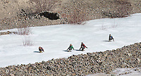 Children slide down a frozen river on makeshift sleds in the Himalayas.