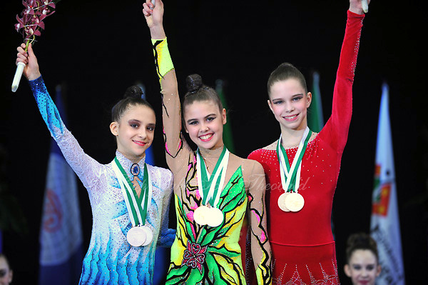 Junior gymnasts (L-R) (wait id) of Germany, Alexandra Merkulova of Russia, Nataliya Leshchyk of Belarus celebrate Event Finals medals at 2010 World Cup at Portimao, Portugal on March 13, 2010.  (Photo by Tom Theobald).