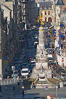 A view over a busy street in Reims (rue Buirette) with a statue monument with a gold painted gilt angel, Reims, Champagne, Marne, Ardennes, France