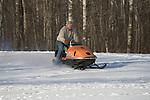 Man driving vintage 1970 AMF Mark V 400 Ski-Daddler snowmobile without helmet