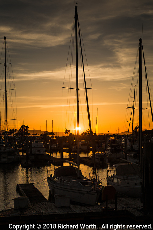 The setting sun is partially hidden by a sailboat mast at the San Leandro Marina on San Francisco Bay.