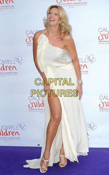 PENNY LANCASTER STEWART.at the Caudwell Children Butterfly Ball at Battersea Evolution, London, England, UK, May 20th, 2010 .full length dress long maxi white cream one shoulder corsage slit split leg thigh sandals smiling .CAP/BEL.©Tom Belcher/Capital Pictures.