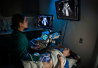Diagnostic Medical Sonography student Brynn O'Hara simulates a patient as fellow student Kaylee Thein performs an ultrasound while practicing for an upcoming exam over spring break.