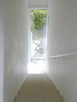 View down a limestone staircase and through the glass wall into the courtyard garden