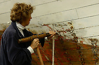 Using a caulking mallet and caulking iron, Joan Madson drives the caulking fabric into the seams of thls boat being restored near Half Moon Bay, California.