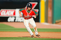 Tony Caldwell (14) of the Greensboro Grasshoppers takes his lead off of first base against the Delmarva Shorebirds at NewBridge Bank Park on May 26, 2013 in Greensboro, North Carolina.  The Grasshoppers defeated the Shorebirds 11-2.  (Brian Westerholt/Four Seam Images)