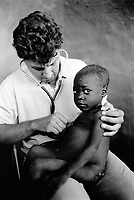 "Mozambique. Province of Tete. Cazula is a small village in the bush. A white doctor (expatriate) with his stethoscope listens to the lungs of a young boy , who sits on the doctor's thighs. Medical consultation. The village can only be reached by plane. Beacause of the war between the Government and the rebel of the Frelimo party, the roads are either mined or too dangerous to travel on. The airplane is part of the  ""Flying Doctors"" programm ran by the non governmental organisation (ngo) Médecins Sans Frontières (MSF) of Belgium.  © 1992 Didier Ruef"
