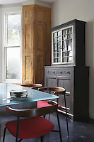 A dresser from a previous home is mixed with a glass-topped table and retro chairs in the dining area of the kitchen