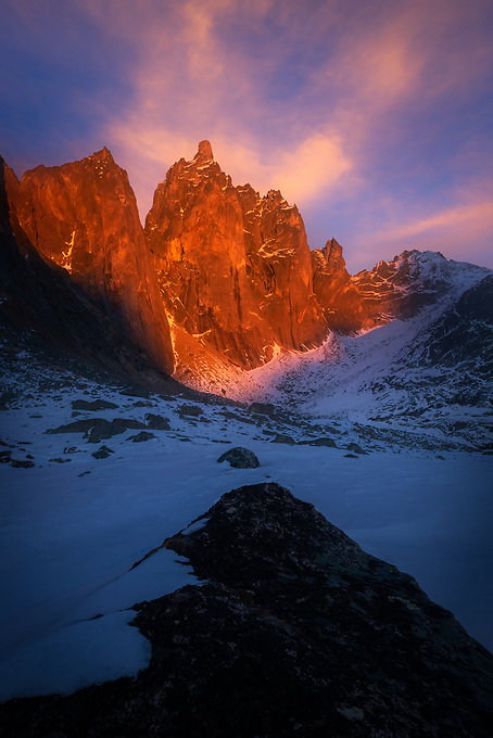 Intense alpenglow just before sunset, shot on the snowy rocks at the base of Mt. Monolith on a cold winter day in Canada's Ogilvie Mountains.