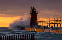 November frozen beach at sunset with snow on the horizon, and pier glowing orange from the sun at South Haven, MI