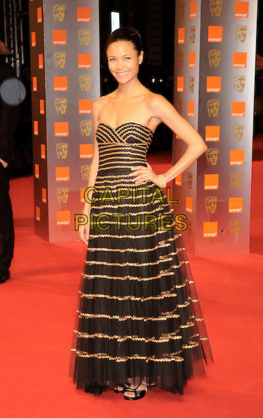 THANDIE NEWTON .The Orange British Academy Film Awards 2009, Royal Opera House, Covent Garden, London, England, February 8th 2009..BAFTAS arrivals full length black gold striped dress strapless hand on hip stripes tulle .CAP/FIN.©Steve Finn/Capital Pictures