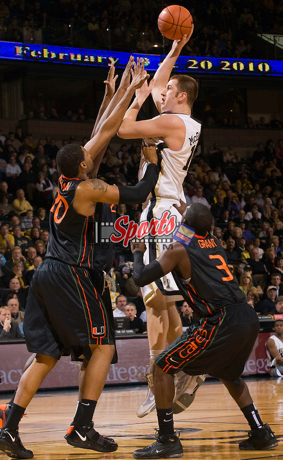 Chas McFarland #13 of the Wake Forest Demon Deacons shoots over Cyrus McGowan #20 and Malcolm Grant #3 of the Miami Hurricanes at the Lawrence Joel Veterans Memorial Coliseum February 2n Winston-Salem, NC.  The Demon Deacons defeated the Hurricanes 64-57.  Brian Westerholt / Sports On Film