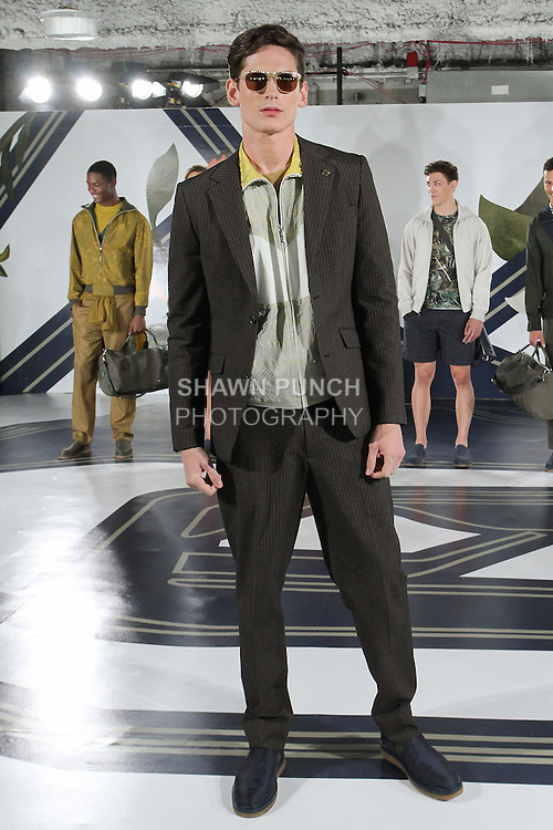 Model Tres poses in a tech-seersucker suit in bark, reflective gyn jacket in yarrow, and mesh t-shirt in Oak Bark tan, from the Perry Ellis Spring 2017 collection by Michael Maccari, on July 11th 2017, during New York Fashion Week Men's Spring Summer 2017.