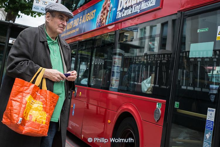 Man waiting at a bus stop, Camden Town, London.