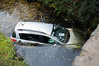 Pictured: A car is half submerged in a canal by Neath Abbey in south Wales, UK.<br /> Re: Police have warned motorists to be vigilant in poor weather conditions after a car ended-up in a canal in Neath Abbey, south Wales.<br /> There are flood alerts in parts of south and west Wales following heavy downpours.<br /> South Wales Police said all occupants of the car were safe after their vehicle plunged into the waterway.