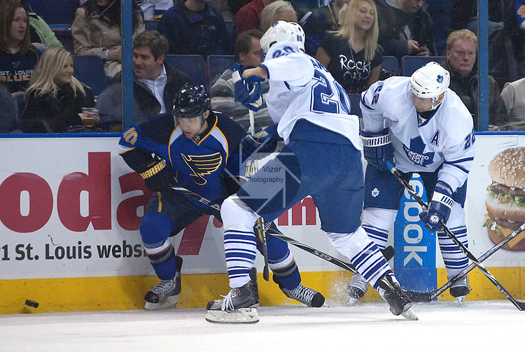 SPO-Maple Leafs vs Blues.12 February 2010 - .ST. LOUIS -                              From left, St. Louis Blues center Andy McDonald (10), Toronto Maple Leafs center Christian Hanson (20), and Toronto Maple Leafs defenseman Francois Beauchemin (22) chase after the puck in the second period.   The Toronto Maple Leafs played the St. Louis Blues at the Scottrade Center in St. Louis, MO, on Friday, February 12, 2010.