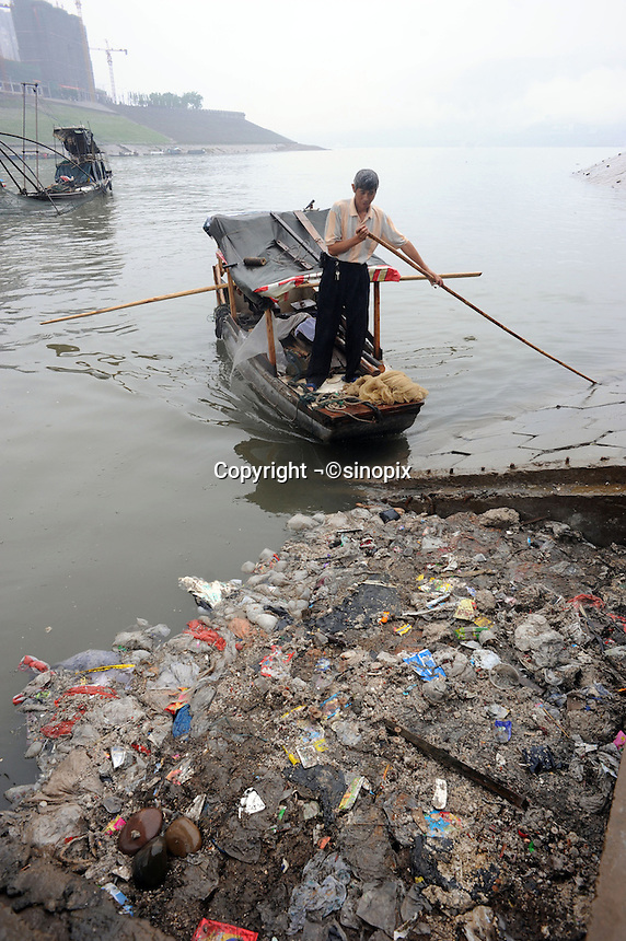 Litter and debris pollutes the Yangtze on the banks of the massive Three Gorges Dam reservoir outside Fengie, China. Several of the new cities are suffering from structural damage due to land and earth movements caused by the 400 km Three Gorges reservoir..27 May 2010