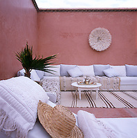 A pink painted open air space with white seating with cushions.