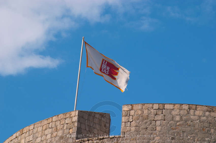 The city flag banner with the slogan Libertas on one of the city wall towers against a blue sky Dubrovnik, old city. Dalmatian Coast, Croatia, Europe.