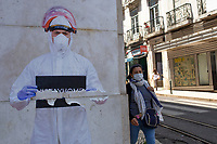 LISBON, PORTUGAL - MAY 18 :  A person using a protective facemask its seen walking by a Stencil of a man in a protective suit in Lisbon, on May 18, 2020. <br /> Restaurants, museums and coffee shops reopen at reduced capacity, while Lisbon eases lockdown coronavirus disease (COVID-19) outbreak.<br /> (Photo by Luis Boza/VIEWpress via Getty Images)