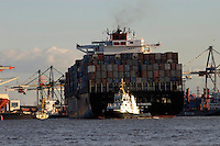 Tugs guiding container ship into harbour, river Elbe, Hamburg, Germany.