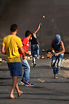 Palestinian protesters throw stones towards Israeli troops during clashes near the Jewish settlement of Bet El, near the occupied West Bank city of Ramallah October 5, 2015. Violence intensified in Jerusalem and the West Bank on Sunday after Israelis were targeted in two stabbing attacks and a Palestinian was killed in a clash with Israeli troops, officials said. Photo by Shadi Hatem