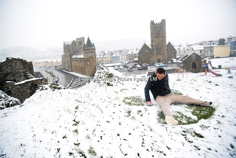 UK Weather: Heavy flurries of snow fall in Aberystwyth, west Wales,  on a cold February morning in Aberystwyth, west Wales, UK. Tuesday 06 February 2018.  TOM PIKE, 23, has fun making a snow angel on the ground, with the castle and town behind him<br /> The Met Office has issued a 'yellow' warning for snow and ice, as a band of sleet and snow moves in from the west, to cover much of Wales and the north of England
