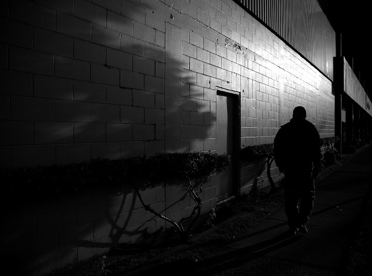 A lone man walking along Venables Street with strange hedge along side of building and contrasting light.