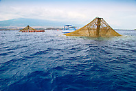 3,000-cubic-meter submersible fish pens installed in open ocean just off Kona Coast to raise Kona Kampachi, Hawaiian yellowtail, aka almaco jack or kahala, Seriola rivoliana, note - the submersible fish pens in raised postion to feed the fish inside, Hualalai volcanic mountain in background, Big Island, Hawaii, Pacific Ocean