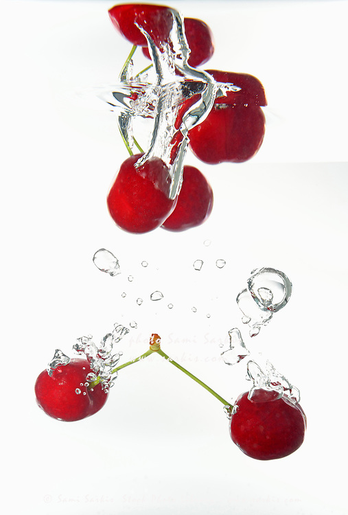 Cherries, fruits splashing underwater, white background, studio