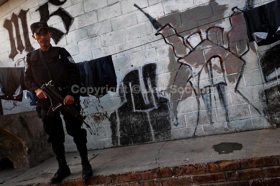 A policeman from the special emergency unit (Halcones) patrols in a gang neighbourhood of San Salvador, El Salvador, 19 May 2011. Although the murder rate in the country has dropped significantly, after a truce between two major street gangs (Mara Salvatrucha and Barrio 18) was agreed in 2012, the lack of security and violence are still the main issues in people's daily life. Due to the fact the gangs have never stopped their criminal activities (extortions, distribution of drugs and kidnappings), the Police anti-gang forces keep running their operations and chasing the 'homeboys' (how the gang's foot soldiers usually call themselves) in the poor, socially deprived suburbs of Salvadoran cities.