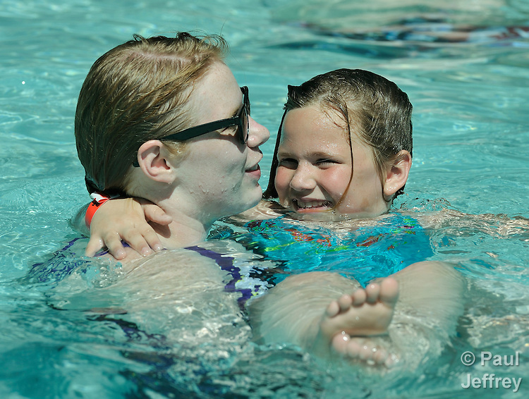 Camper Kaylee Ferguson is supported by counselor Kelsey Samples in the swimming pool at Camp Aldersgate in Little Rock, Arkansas. The camp, supported by United Methodist Women, offers children suffering from a variety of disabilities a safe and fun experience similar to that which normally-abled children often enjoy.