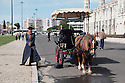 Lisbon, Portugal. 16.04.2016. Woman with horse and carriage, outside the Mosteiro dos Jerónimos (Jeronimos Monastery), Belem, Lisbon. Photograph © Jane Hobson.